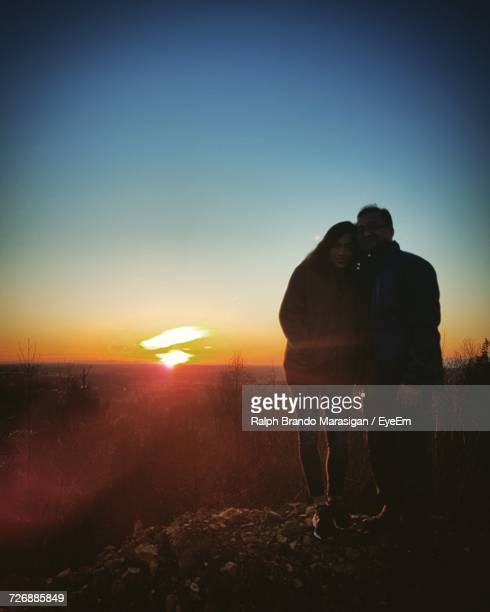 Couple Standing On Hill Against Sky During Sunset