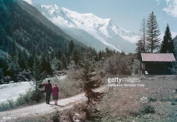 Couple standing on path near river looking out to mountains