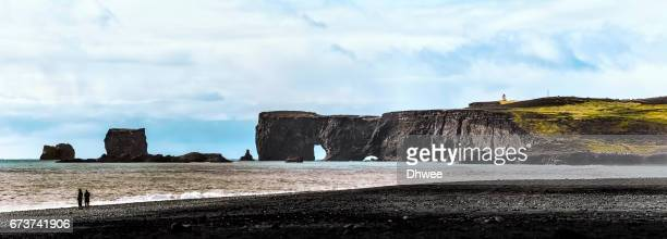 Couple Standing On Reynisfjara Beach With Dyrholaey Cliffs At Background, Iceland