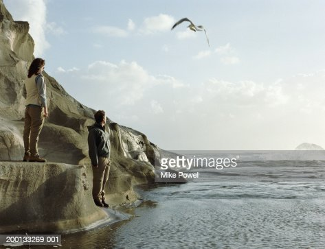 Couple standing on rock formation on beach : Stock Photo