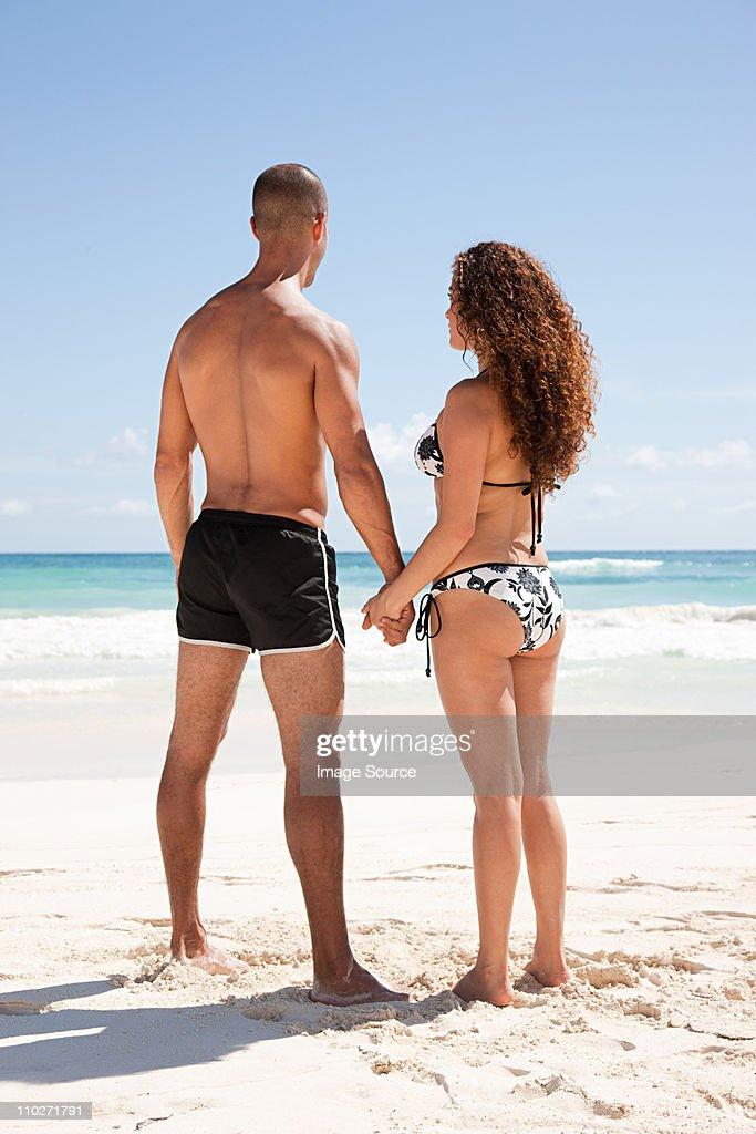 Couple standing on sandy beach