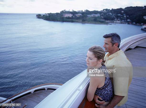 Couple standing on ships deck, looking over rail