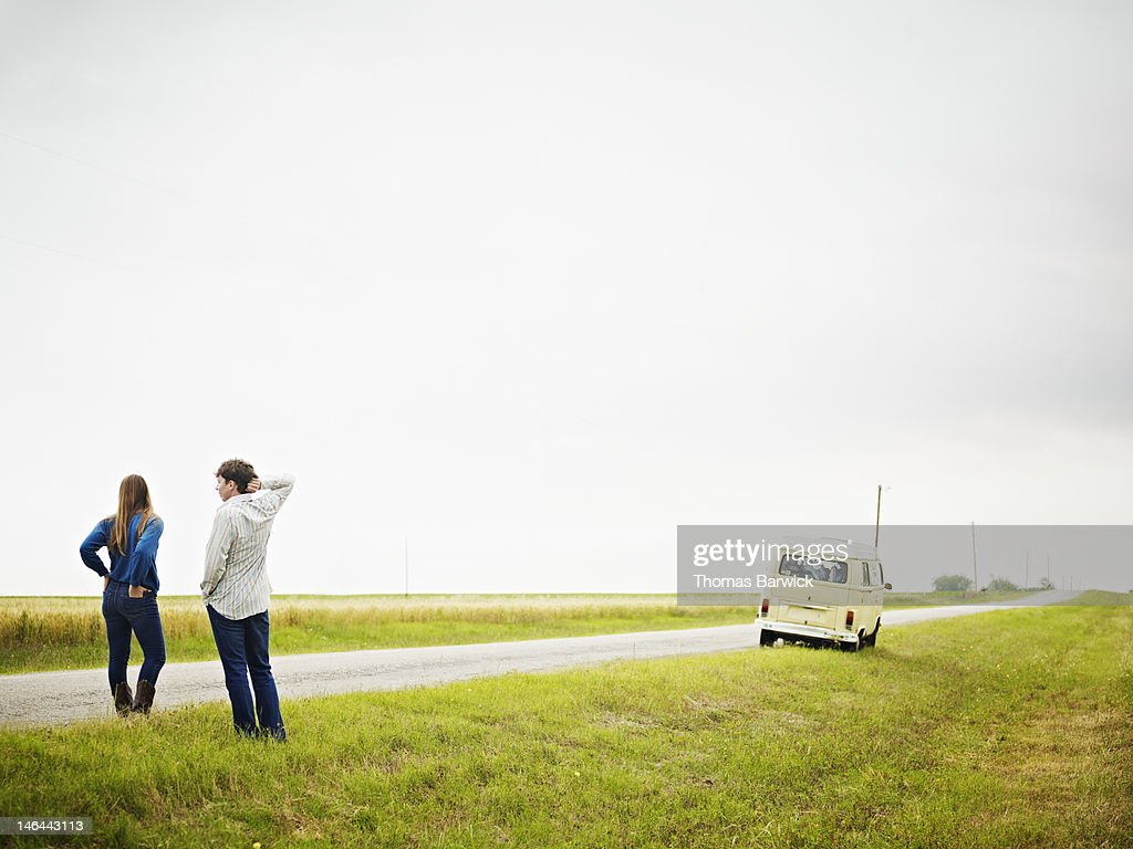 Couple standing on side of rural road : Stock Photo