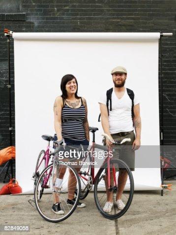 Couple standing on sidewalk holding bikes