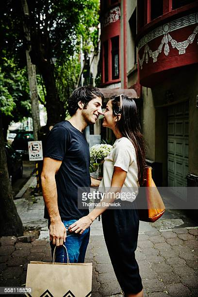 Couple standing on sidewalk leaning in to kiss