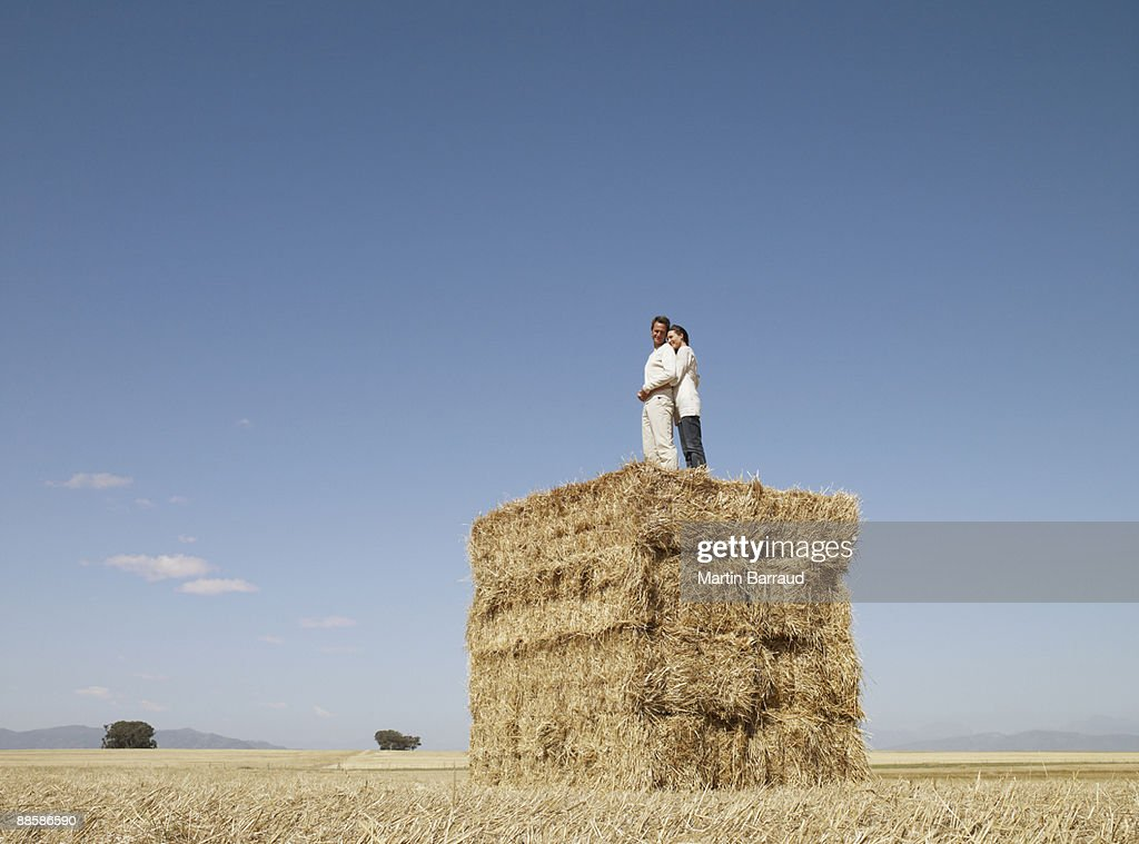 Couple standing on stack of hay bales : Stock Photo