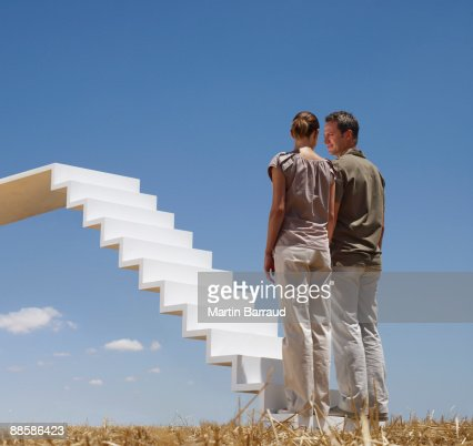 Couple standing on stairway over field : Stock Photo
