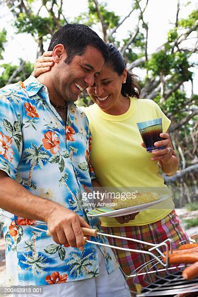 Couple standing outdoors, man tending barbecue, smiling