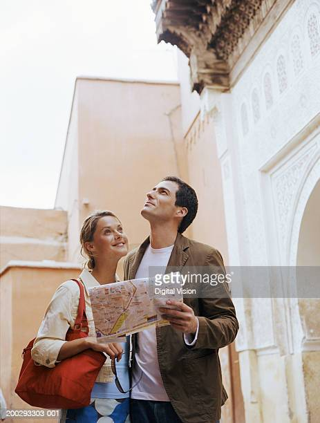 Couple standing outdoors smiling, man holding map