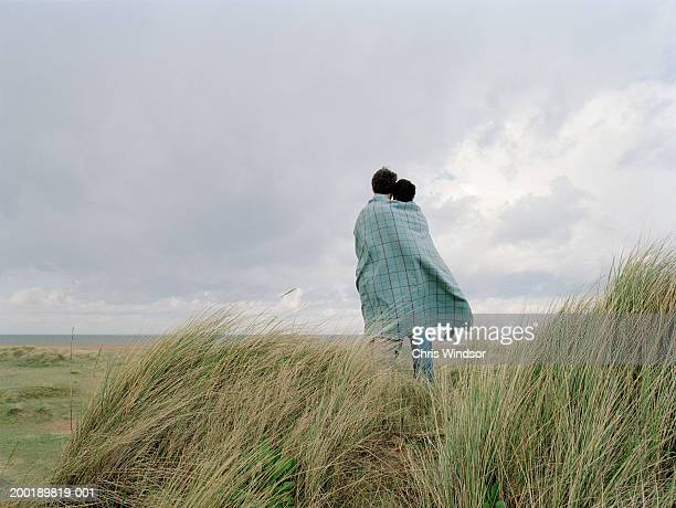 Couple standing outdoors under blanket, rear view