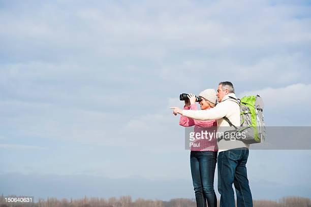Couple standing outdoors with binoculars