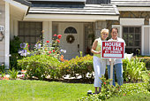 Couple Standing Outside House With Real Estate Sign