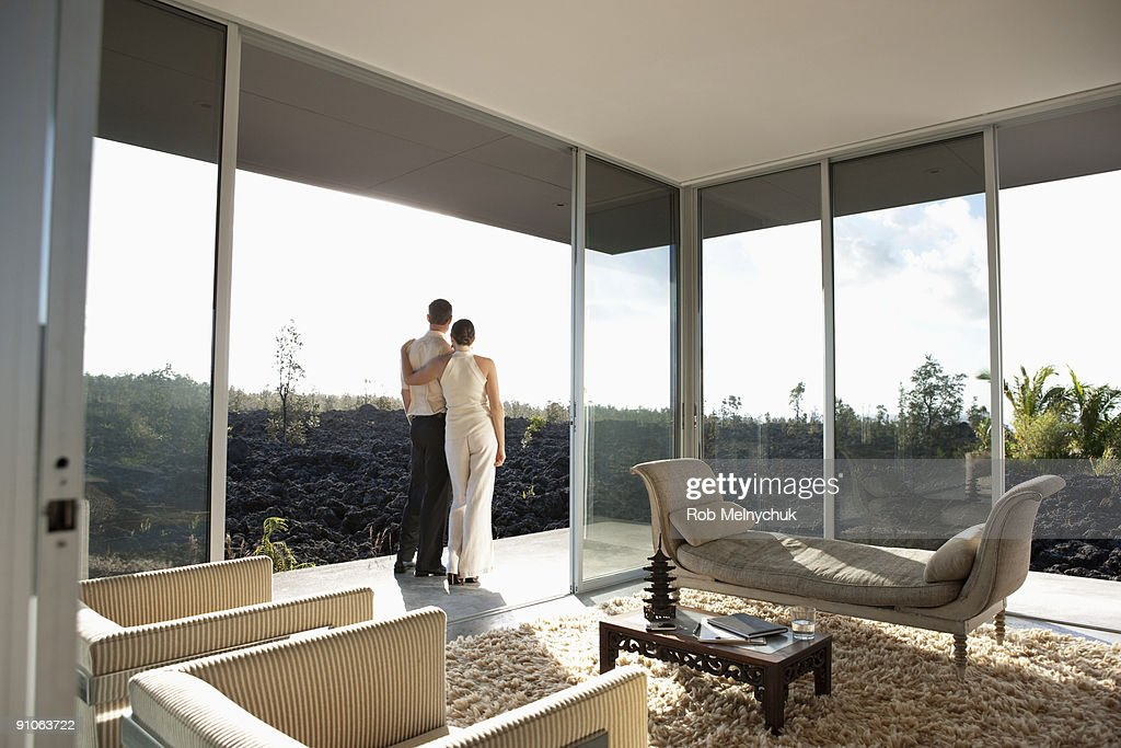 Couple standing outside modern room, admiring view : Stock Photo