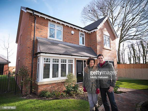 Couple standing outside of energy efficient house