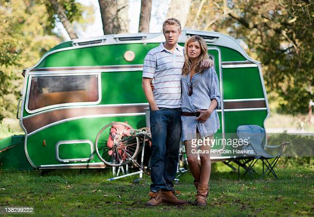 Couple standing outside trailer in park