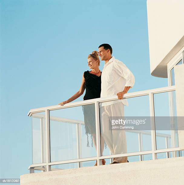 Couple Standing Side by Side on a Modern Balcony