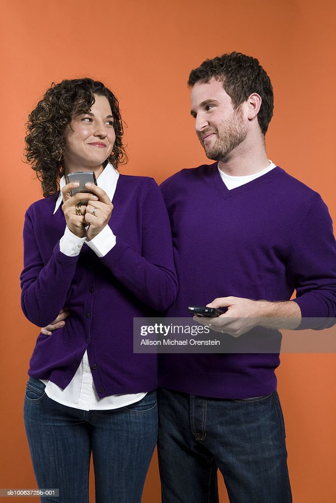 Couple standing together and holding mobile phones : Stock Photo
