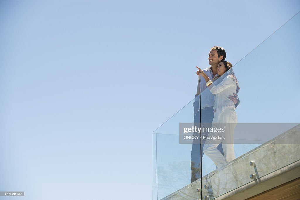 Couple standing together on a terrace and pointing away
