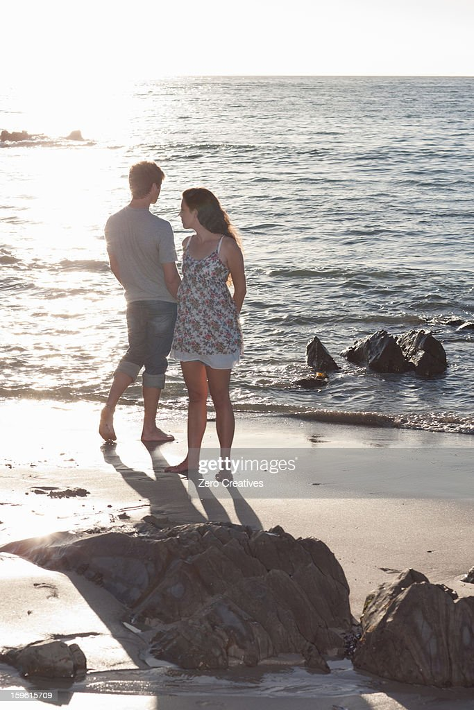 Couple standing together on beach : Stock Photo