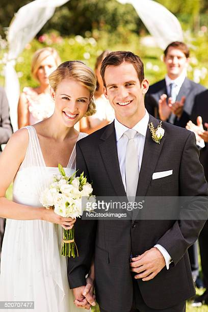 Couple Standing Together With Guests At Garden