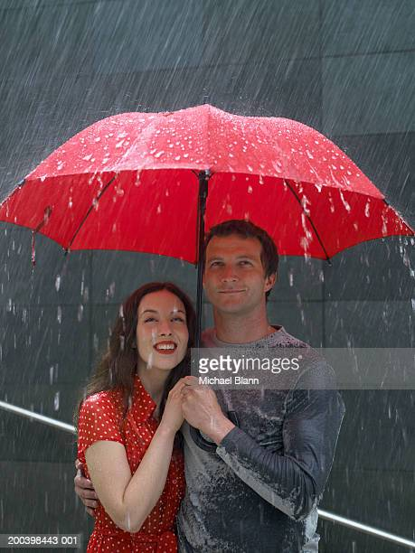 Couple standing under umbrella in rain, looking up, close-up