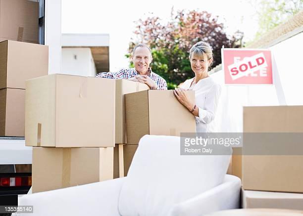 Paar stehend mit Kartons und moving van