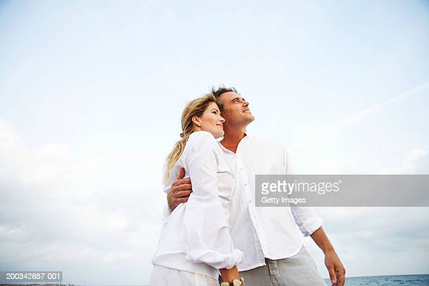 Couple standing with heads together, smiling, low angle view