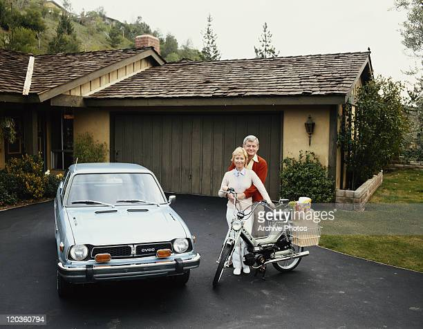 Couple standing with Puch moped and Honda Civic, smiling