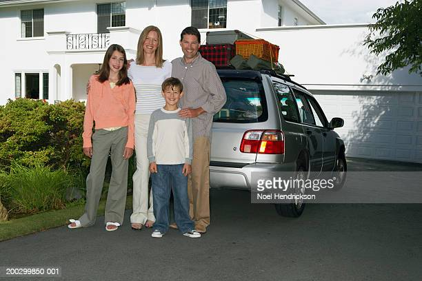 Couple standing with son and daughter (8-13 years) beside car in front drive