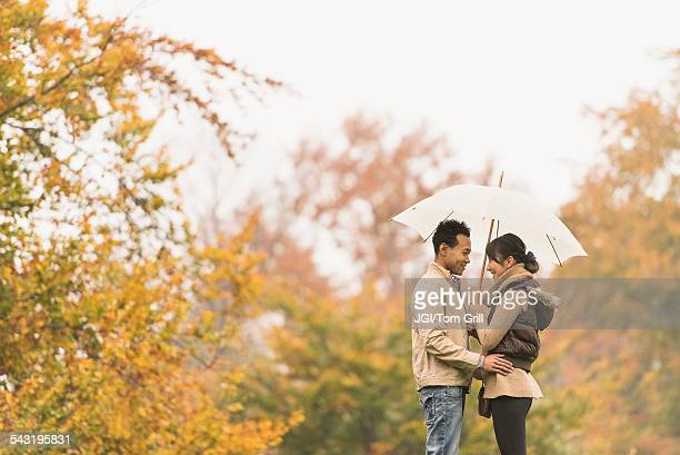 Couple standing with umbrella in park