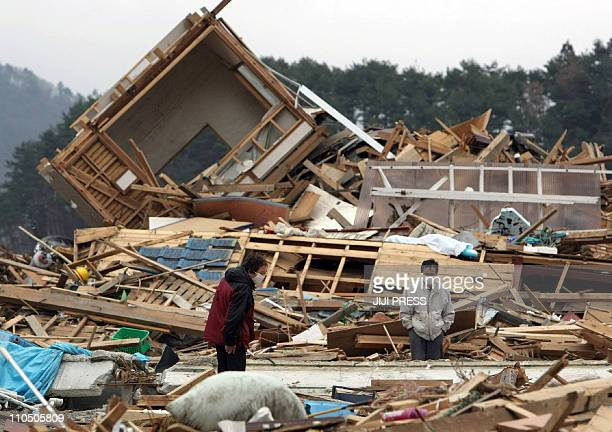 A couple stands in the rubble of there their house was before the March 11 tsunami in the city of Ishinomaki in Miyagi prefecture on March 21 2011 10...