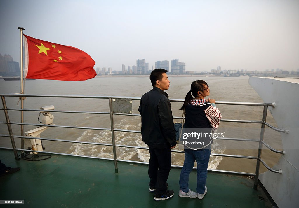 A couple stands near a Chinese national flag on a ferry crossing the Chang Jiang river in Wuhan, China, on Sunday, Oct. 20, 2013. China's economic expansion accelerated to 7.8 percent in the third quarter from a year earlier, the statistics bureau said Oct. 18, reversing a slowdown that put the government at risk of missing its 7.5 percent growth target for 2013. Photographer: Tomohiro Ohsumi/Bloomberg via Getty Images