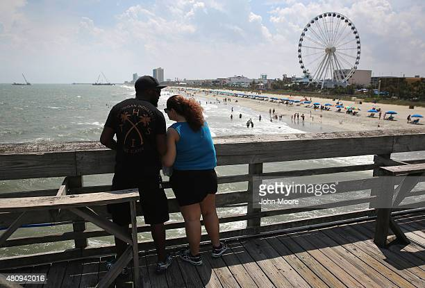 A couple stands on a pier overlooking the beach and the SkyWheel on July 13 2015 in Myrtle Beach South Carolina The 187 foot tall ferris wheel built...