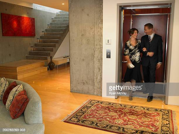 Couple stepping off elevator into living room (blurred motion)
