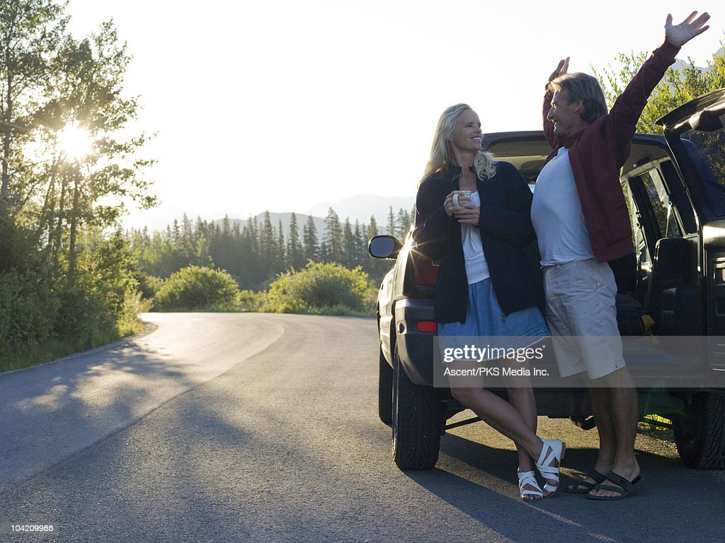 Couple stop for morning coffee/stretch by roadside : Stock Photo
