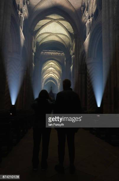 A couple stop to take a picture as the inside of the historic Durham Cathedral is illuminated by a light installation titled 'Methods' by artist...
