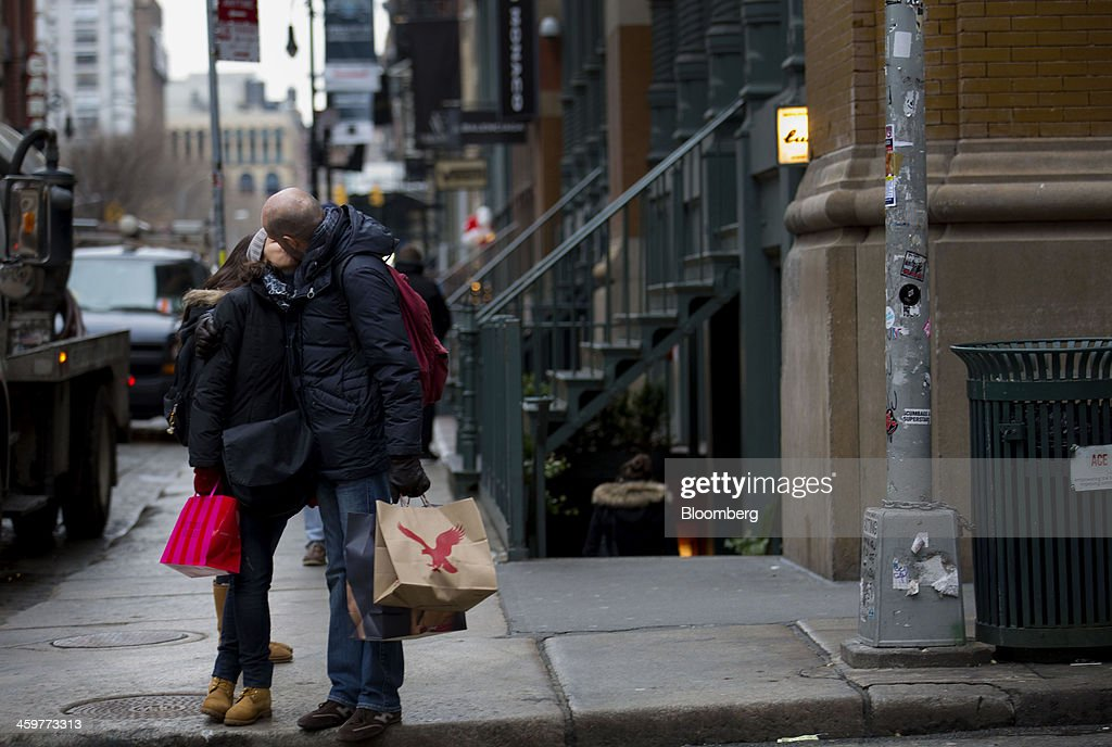 A couple stops for a kiss while shopping in the Soho neighborhood of New York, U.S., on Monday, Dec. 30, 2013. The failure of United Parcel Service Inc. (UPS) and FedEx Corp. to deliver packages in time for Christmas has exposed the perils of retailers promising to get last-minute gifts to customers. Photographer: Jin Lee/Bloomberg via Getty Images