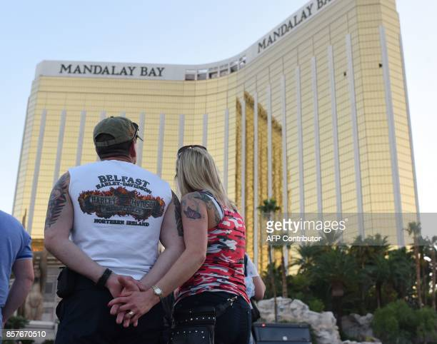 A couple stops on the Las Vegas Strip October 4 to look up at the two broken window in the Mandalay Bay hotel from which killer Stephen Paddock let...