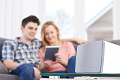 Couple Streaming Music From Digital Tablet To Wireless Speaker