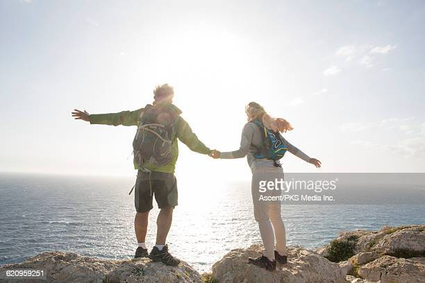 Couple stretch arms out on bluff above sea, windy