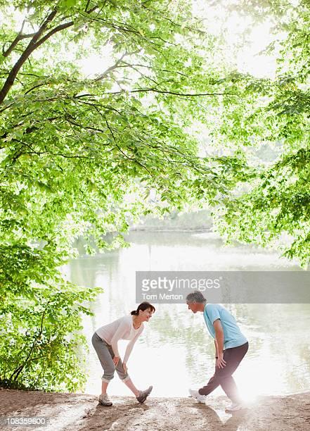 Couple étirement avant de sport à proximité du lac