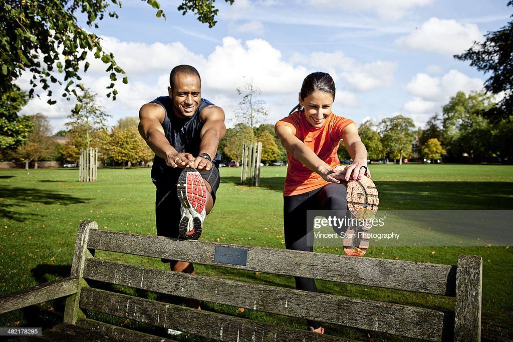 Couple stretching legs on park bench