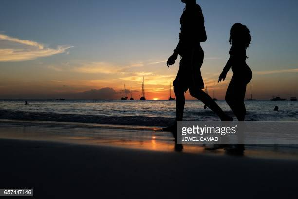 A couple stroll along a beach as the sun sets in Bridgetown Barbados on March 24 2017 / AFP PHOTO / Jewel SAMAD
