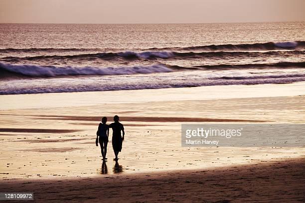 Couple strolling along Seminyak Beach. Oberoi Hotel. Denpasar. Bali, Indonesia.