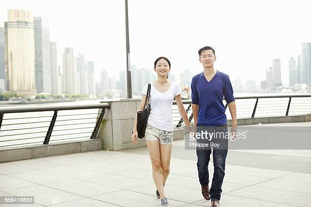 Couple strolling hand in hand on the waterfront, The Bund, Shanghai, China