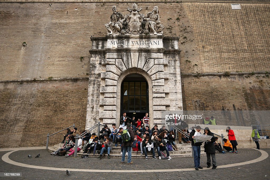 A couple study a street map as tourists sit on steps outside the Vatican Museum ahead of Pope Benedict XVI's last public audience on February 26 2013...
