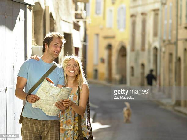 Couple studying map in street