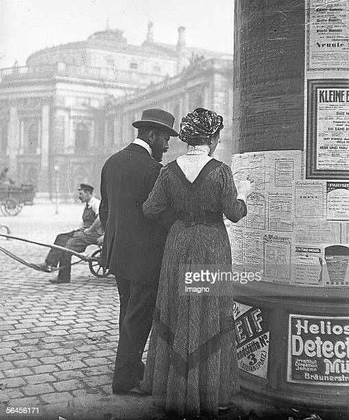 Couple studying the theater program hanging at an advertising column opposite to the Burg Theater Vienna Photography by Emil Mayer around 1910...
