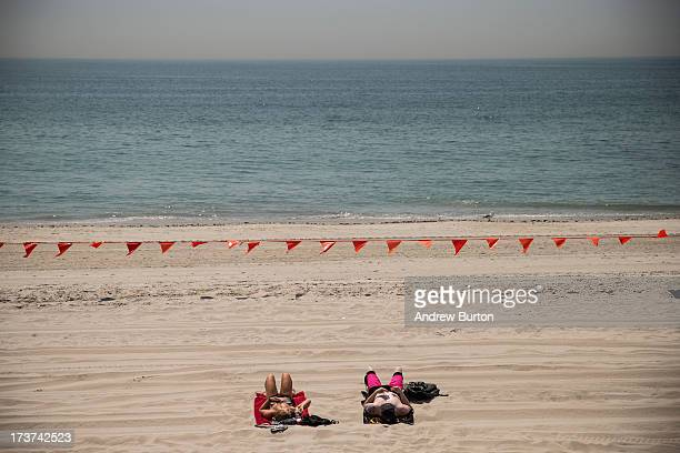 A couple sunbathes at Rockaway Beach during a heat wave on July 17 2013 in the Rockaway Beach neighborhood of the Queens borough of New York City...