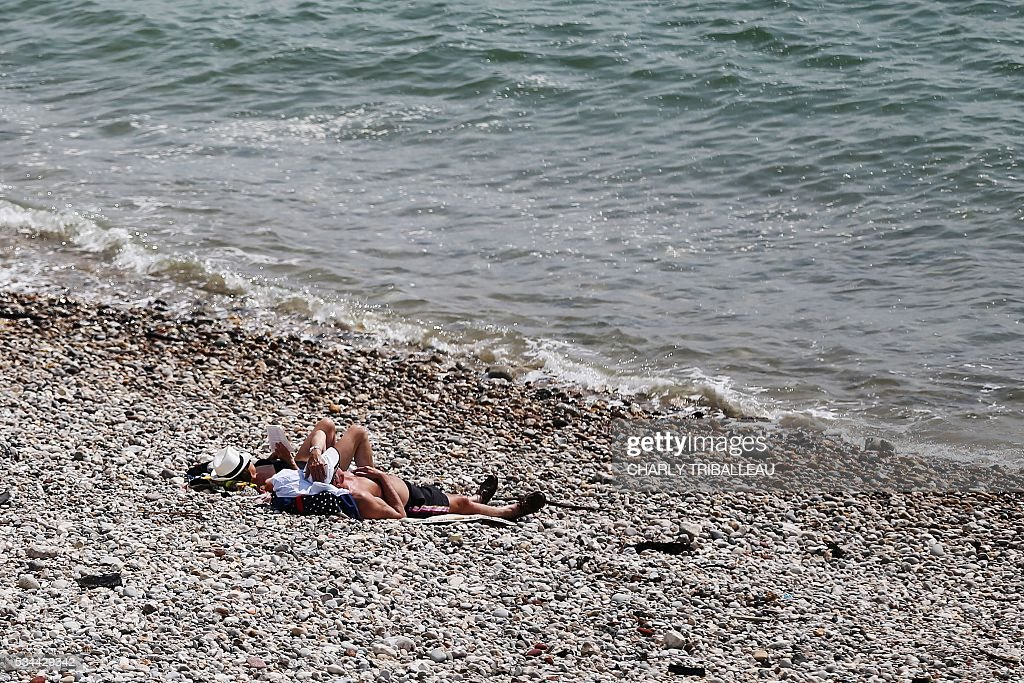 A couple sunbathes on the beach on May 26, 2016 in Le Havre, northwestern France. / AFP / CHARLY